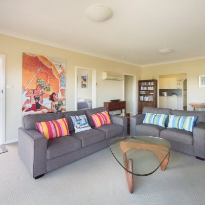 Front living room & balcony at Southerly Change, holiday house rental accommodation at Gerroa, Seven Mile Beach